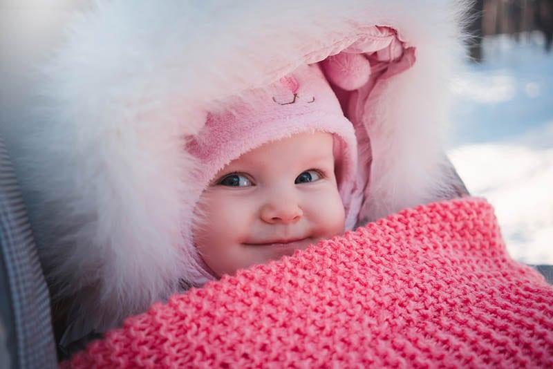 süßes Baby Mädchen in Winterjacke und Hut lächelnd