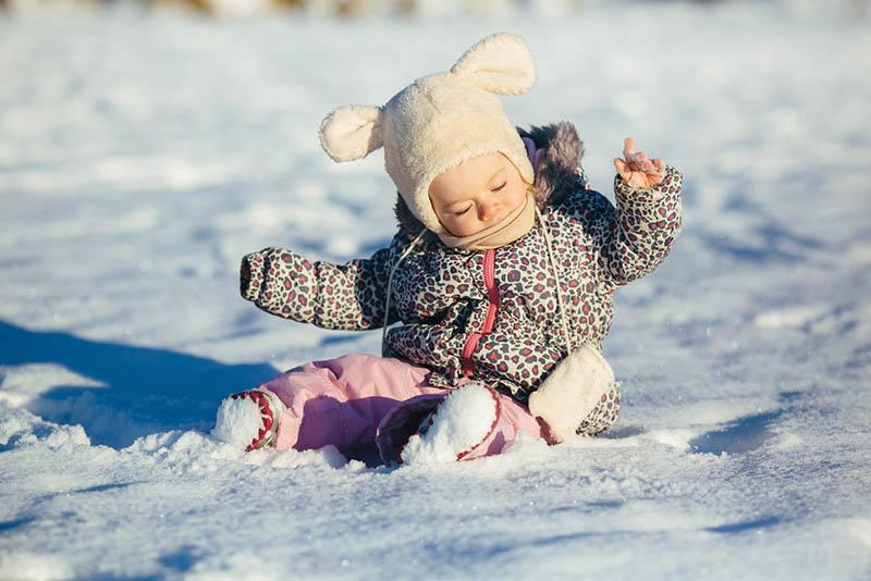 süßes Baby Mädchen spielen auf dem Schnee