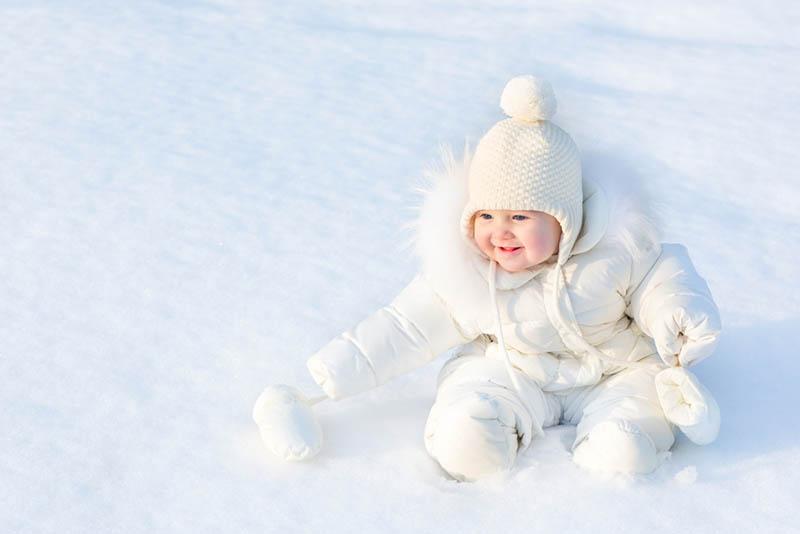 süßes Baby in weißen Winteranzug sitzt auf dem Schnee