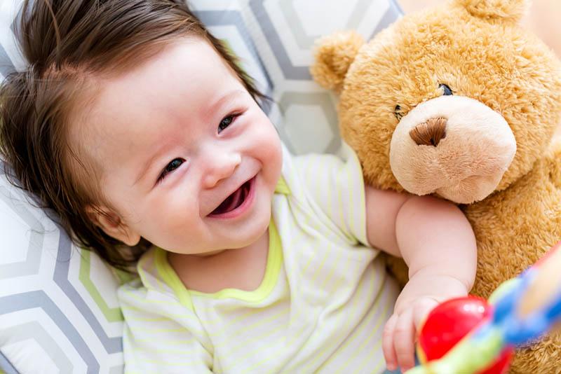 süßes Baby lächelnd und liegend mit Teddybär