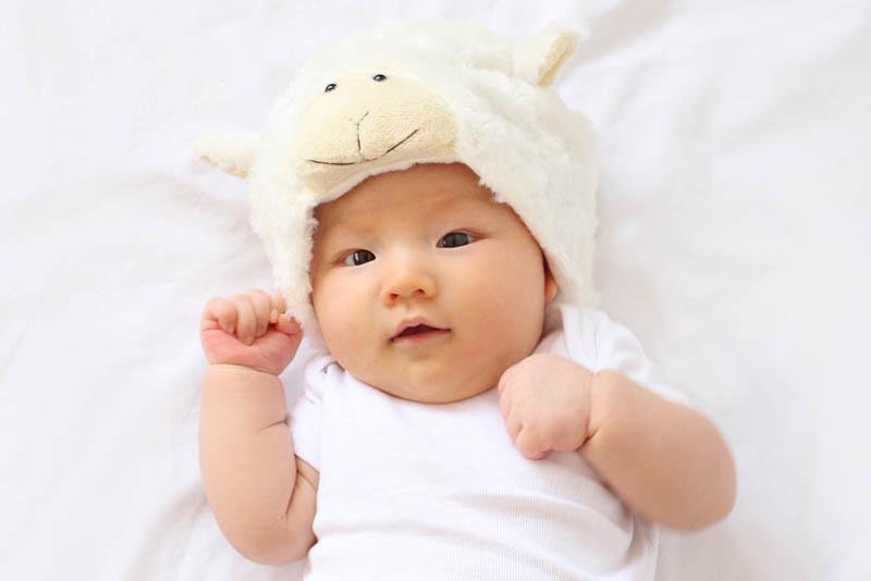 süßes Baby mit Schafsmütze auf dem Bett