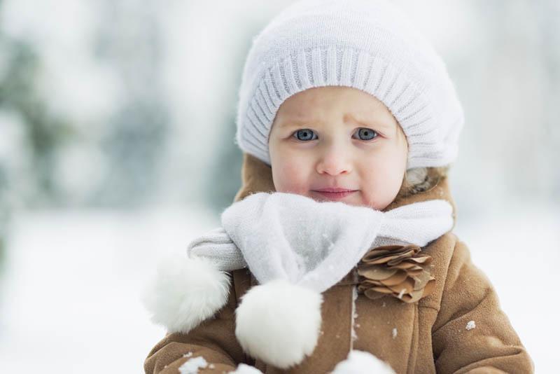 süßes kleines Mädchen im Winterpark stehend