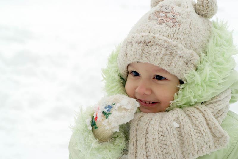 süßes kleines Mädchen in Winterkleidung essen Schnee