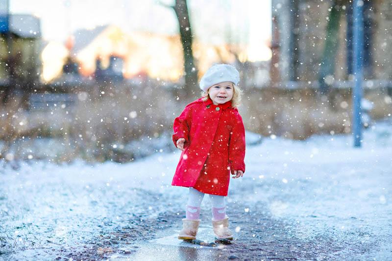 süßes kleines Mädchen in rotem Mantel stehend im Schnee