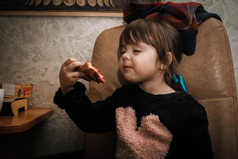 süßes kleines Mädchen mit Schleife auf dem Kopf isst ein Pizzastück