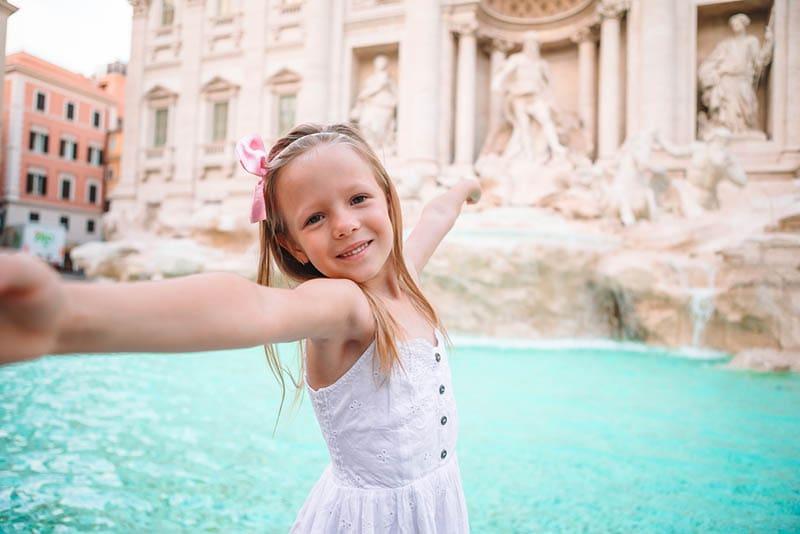 süßes kleines Mädchen posiert vor Brunnen in Rom