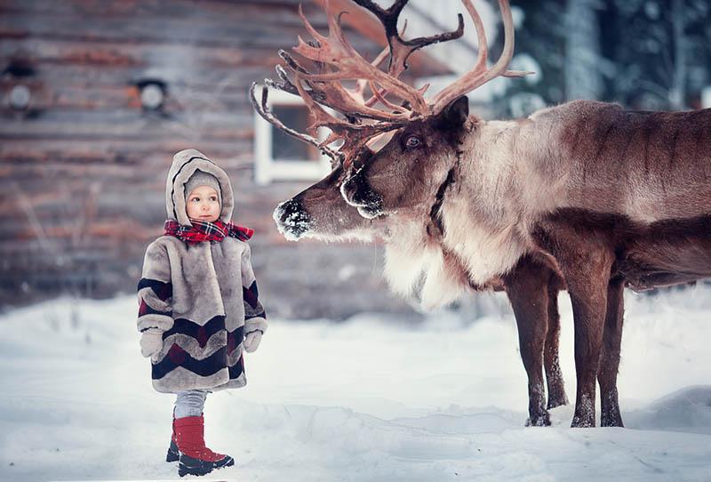 süßes kleines Mädchen stehend mit Rentieren im Freien