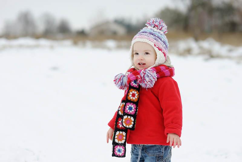 süßes kleines Mädchen trägt bunte Kleidung stehen im Freien im Schnee