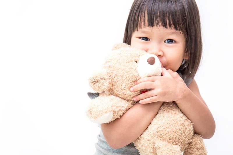 süßes kleines Mädchen umarmt Teddybär