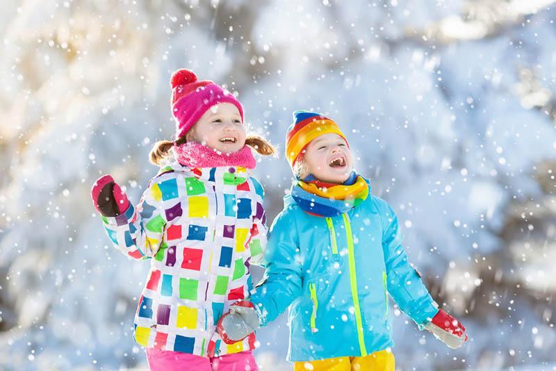zwei kleine Mädchen, die den Schnee im Freien genießen