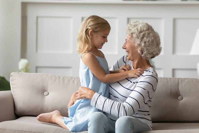 Ältere Großmutter verbringen angenehme Zeit mit hübscher Enkelin
