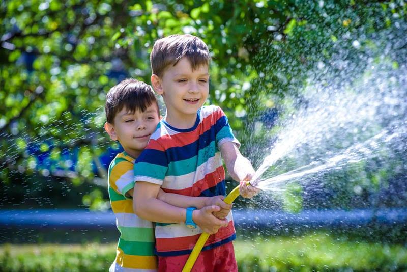 Brüder haben Spaß spritzen sich gegenseitig mit Wasser