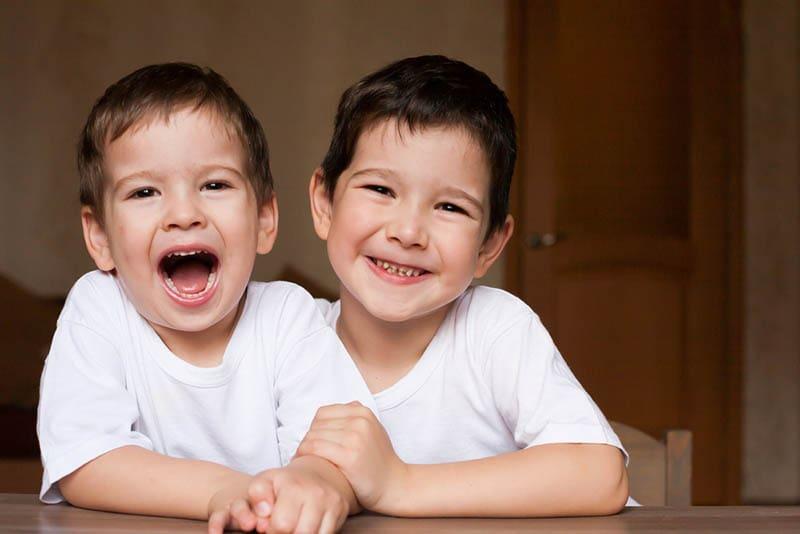 Brüder lächelnd beim Sitzen am Tisch