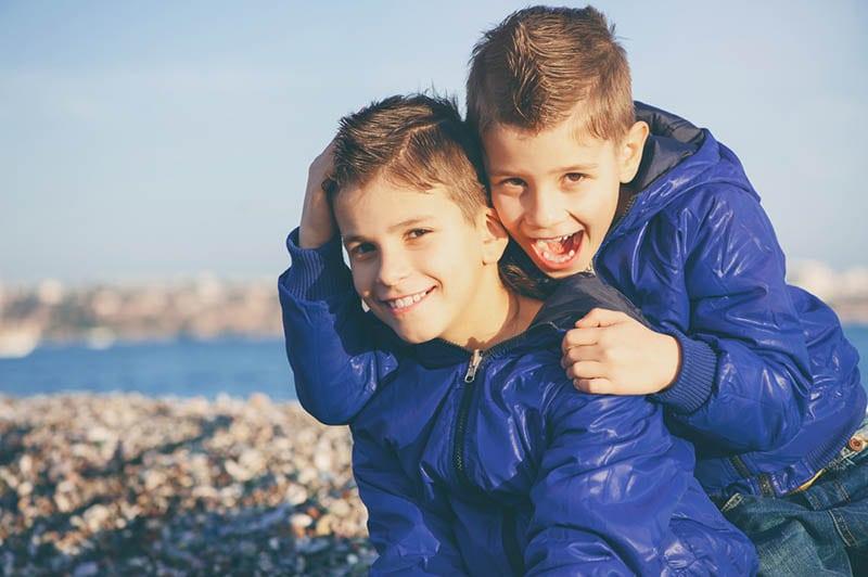Brüder umarmen und lächelnd am Strand im Winter