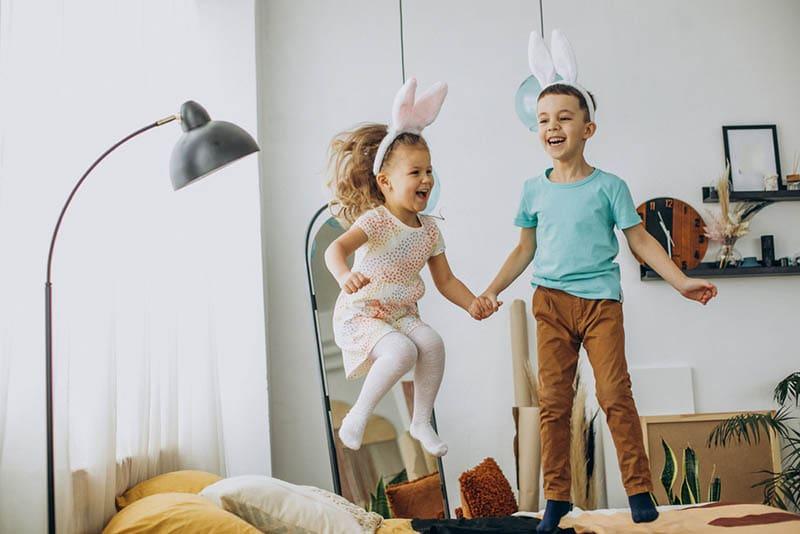 Bruder und Schwester halten Hände und springen auf dem Bett