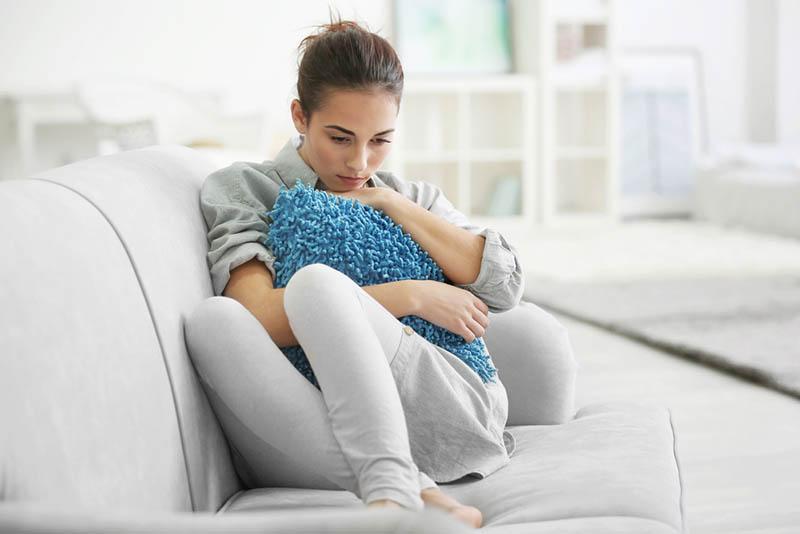 Depressive junge Frau auf Sofa zu Hause