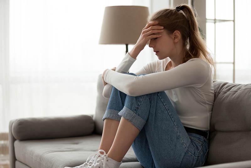Depressive junge Frau sitzt auf der Couch und hält für den Kopf