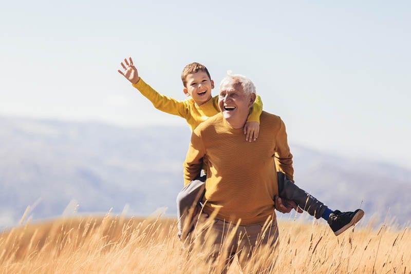 Enkel Huckepack mit seinem Großvater auf dem Feld