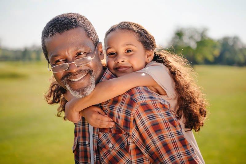 Enkelin umarmt ihren lächelnden Großvater auf grünem Rasen