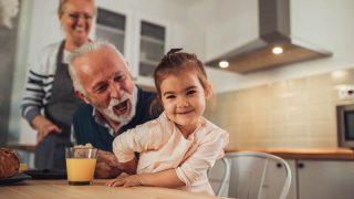 niedlichen kleinen Mädchen lächelnd in der Küche mit Großeltern