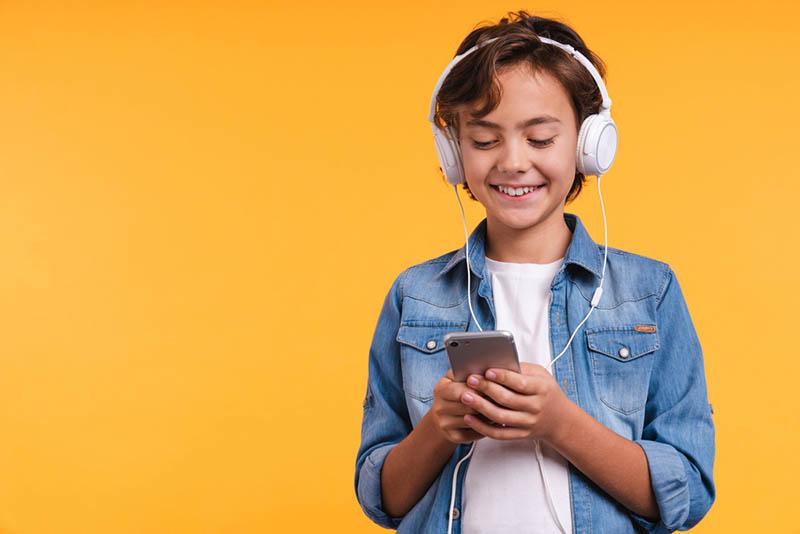 Fröhlicher Junge hört mit Kopfhörern der Musik zu