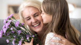 Kleine Enkelin küsst Oma auf die Wange und gibt ihr violette Blumen