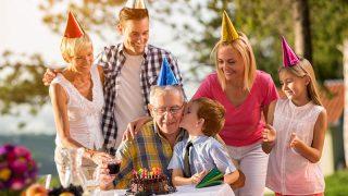 Fröhliche Familie feiert den Geburtstag des Großvaters im Freien