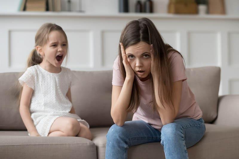 Gestresste erschöpfte Mutter sitzt auf der Couch, während das kleine Mädchen schreit