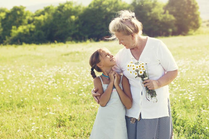 Glückliche Großmutter steht mit ihrer Enkelin in der Wiese