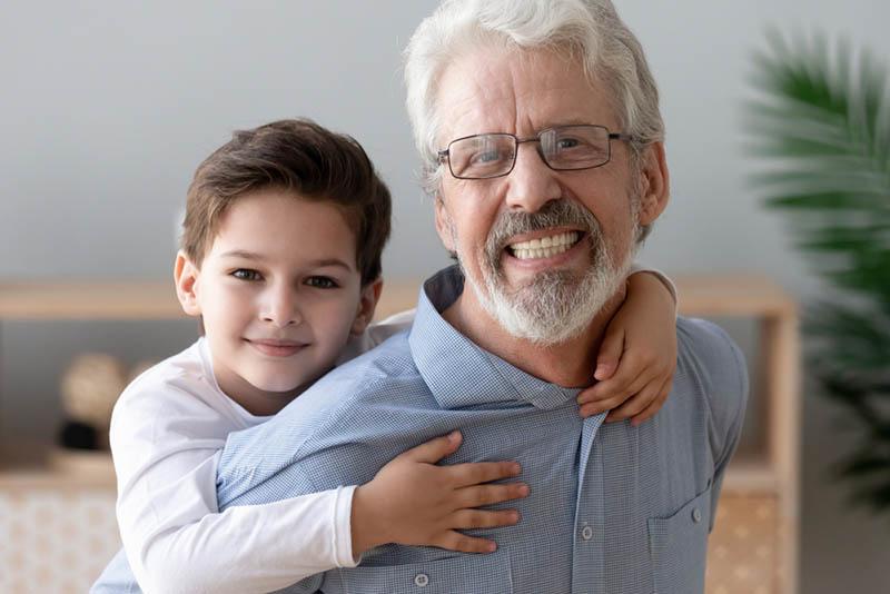 Glücklicher alter Großvater hält kleinen Enkel auf dem Rücken