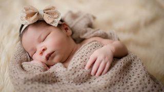 neugeborenes Mädchen schläft und hat eine Schleife auf dem Kopf