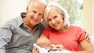 glückliche Großeltern posieren mit neugeborenem Baby