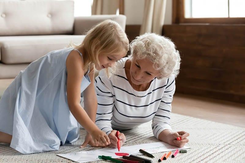 Großmutter Zeichnung auf dem Boden mit Enkelin