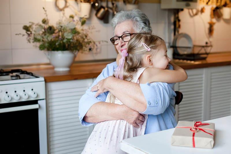 Großmutter ist umarmt Kind Mädchen in gemütlichen Küche zu Hause