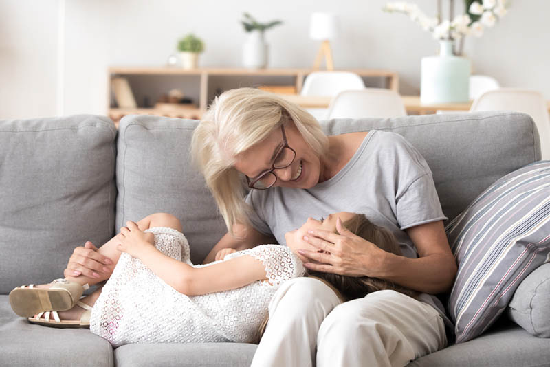 Großmutter kuschelt mit ihrer Enkelin auf der Couch