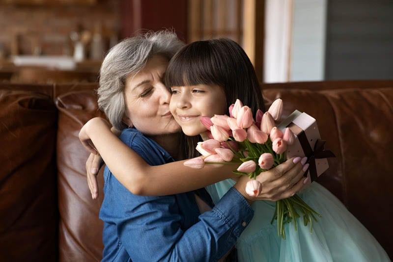 Großmutter küsst kleines Mädchen, während sie Blumen hält