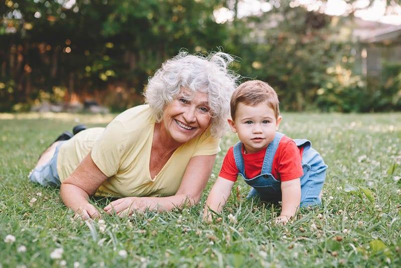 Großmutter liegend auf Gras mit Enkelsohn