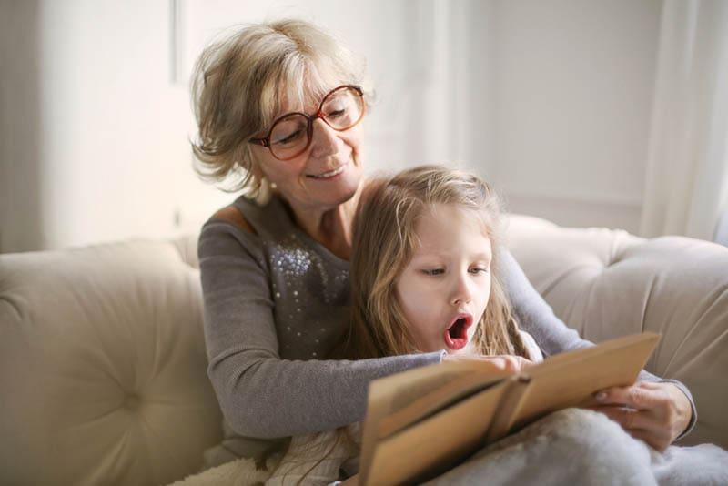 Großmutter liest ein Buch mit Enkelin auf der Couch
