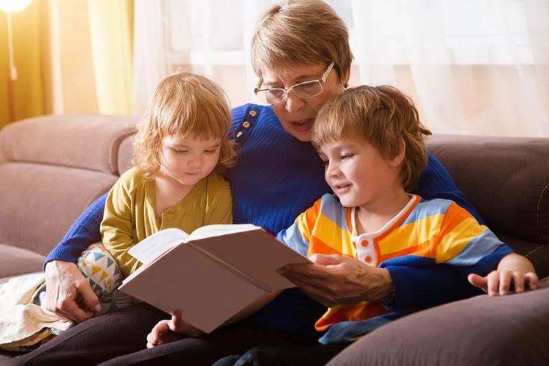 Großmutter liest ihrem Enkel und ihrer Enkelin ein Märchen vor