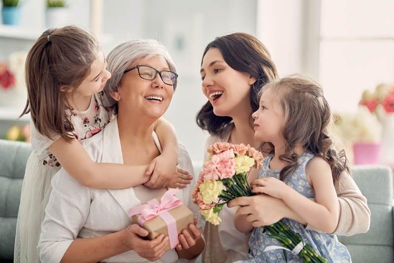 Großmutter mit ihrer Tochter und Enkelin mit Geburtstagsgeschenken