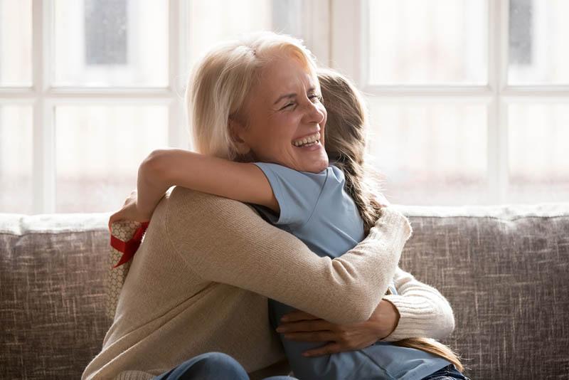 Großmutter umarmt Enkelin fest auf der Couch zu Hause