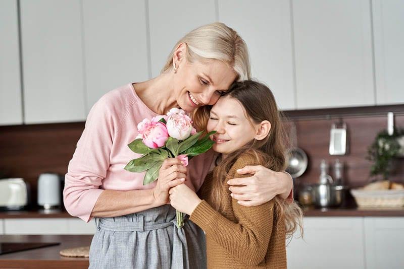 Großmutter umarmt er kleine Enkelin in der Küche