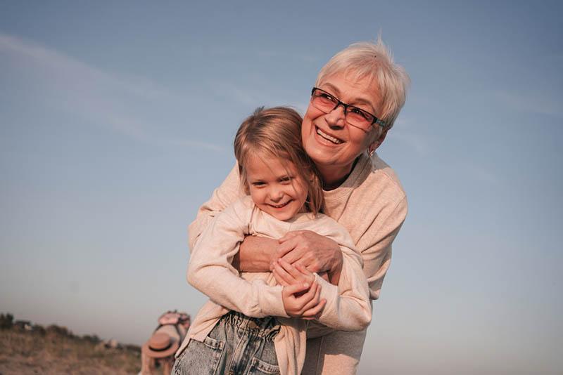 Großmutter umarmt ihre Enkelin und lächelt