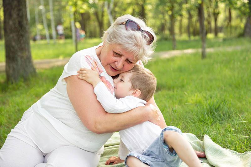 Großmutter umarmt mit Enkel im Park