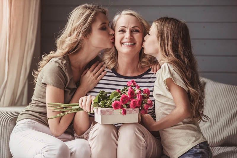 Großmutters Tochter und Enkelin küssen sie auf die Wangen