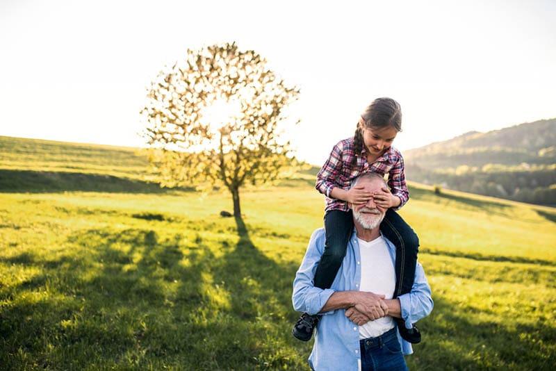 Großvater gibt eine kleine Enkelin eine Huckepackfahrt in der Natur