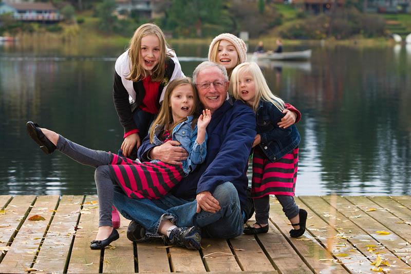 Großvater posiert mit seinen Enkelkindern am See