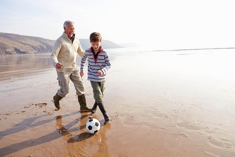 Großvater und Enkel spielen Fußball am Winterstrand