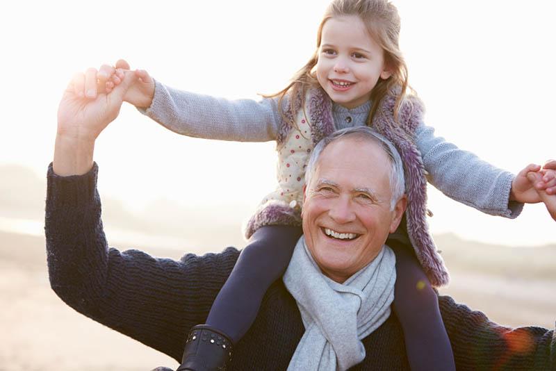 Großvater und Enkelin zu Fuß auf Winter Strand
