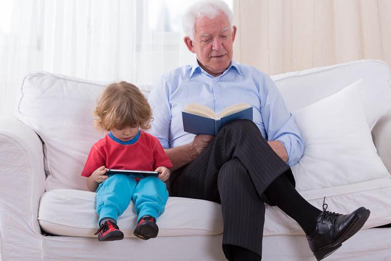 Großvater und Enkelkind sitzen auf dem Sofa und lesen Bücher